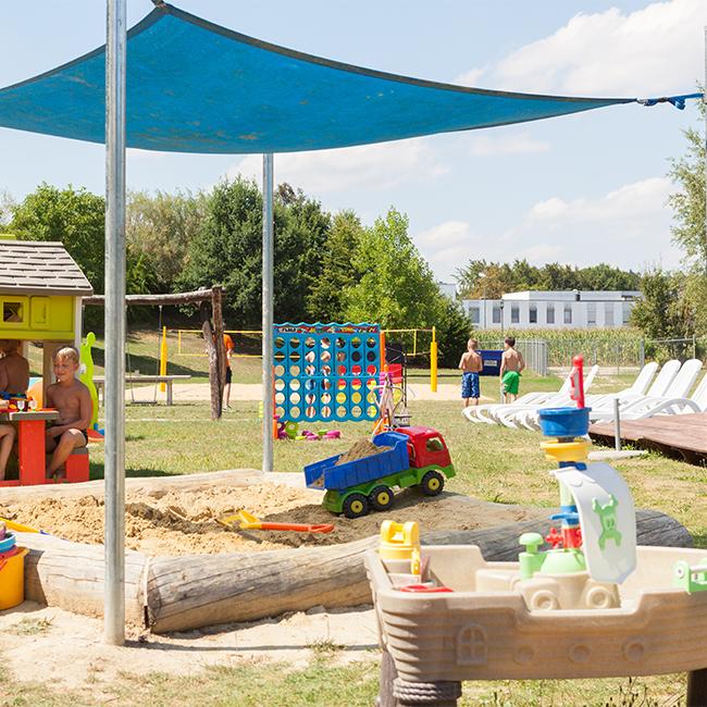 Spielplatz draußen mit Sandkasten und Liegefläche
