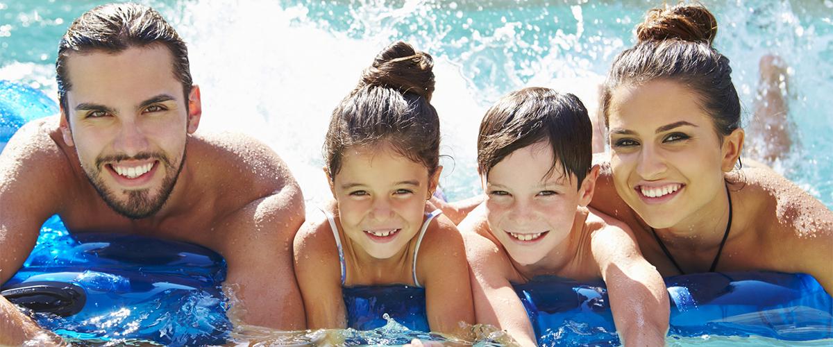 Familie auf einer Luftmatratze planschend im Wasser