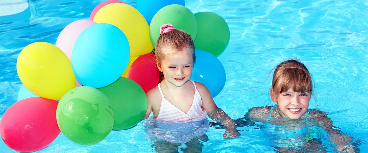 zwei Kinder mit Ballons im Wasser