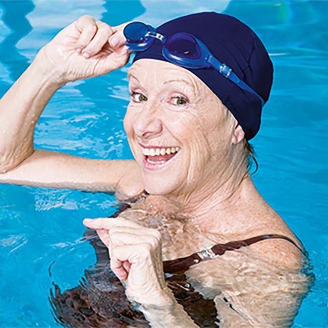 ältere Dame im Wasser mit Taucherbrille und Badekappe
