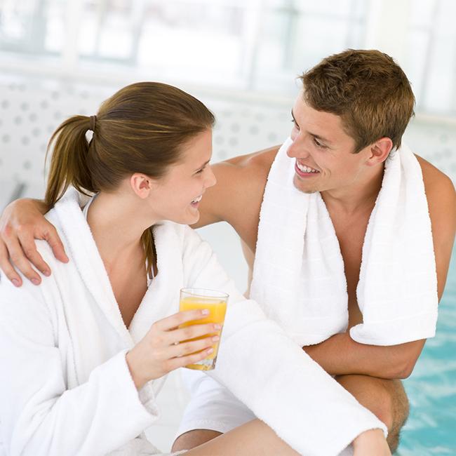 zwei Studeten in Bademantel und Handtuch lächelnd im Schwimmbad
