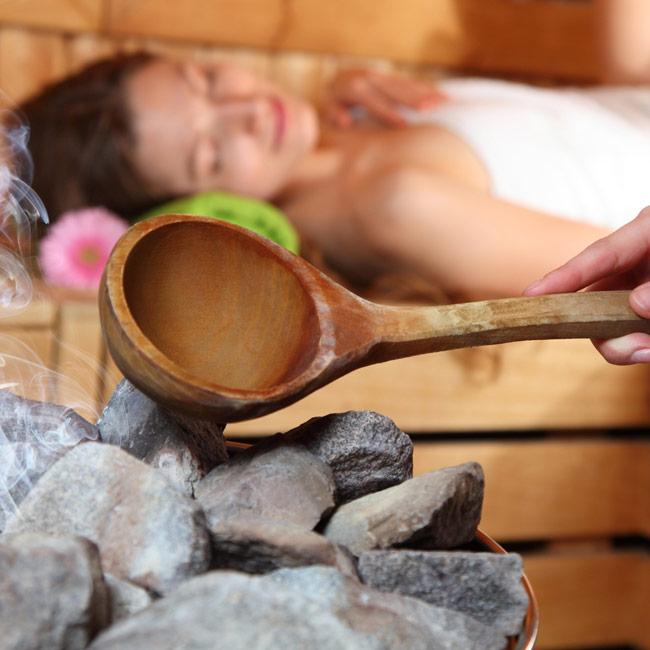 entspannte Dame beim Saunaaufguss mit Steinen und Kelle