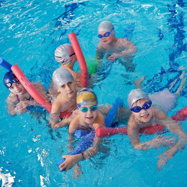 Kinder mit Schwimmnudeln, Taucherbrillen und Bademützen im Wasser
