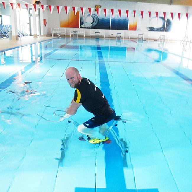 Aquakurs-Trainer auf Trainingsrad im Wasser