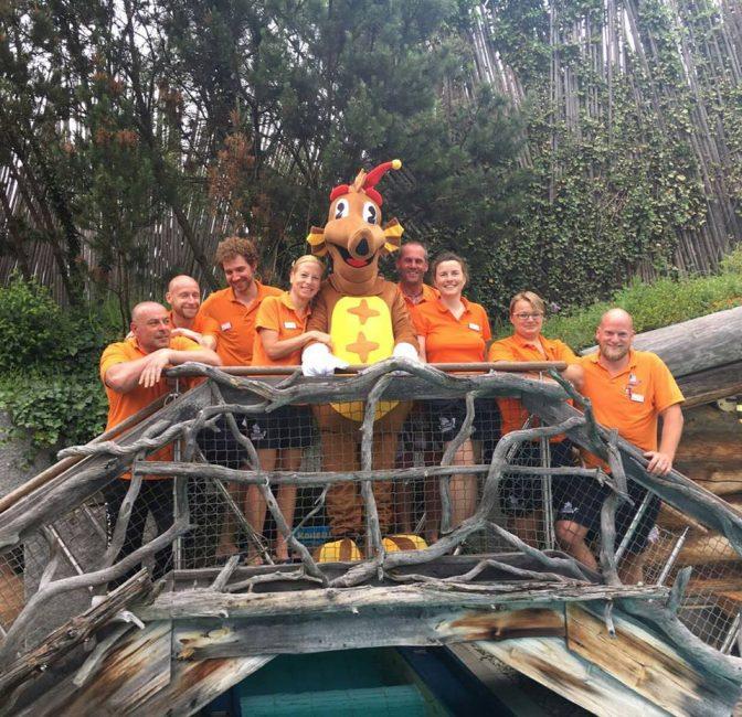 Tikki-Maskottchen und Mitarbeiter auf Holzbrücke Außenbereich