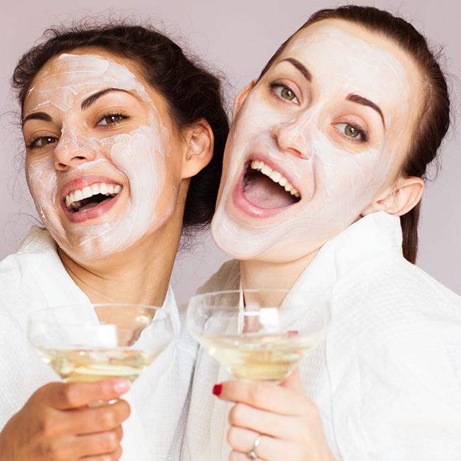 zwei lachende Damen mit weißer Gesichtsmaske und Sektgläsern