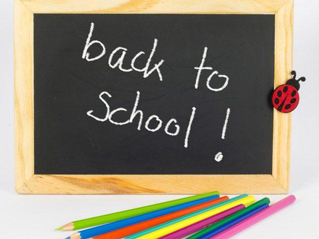 Schultafel mit der Aufschrift back to school und bunten Stiften