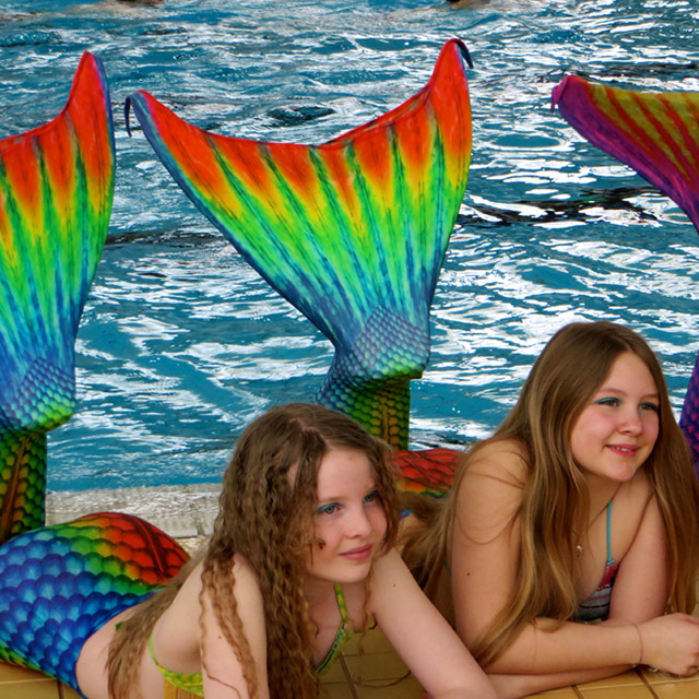 Mädchen mit Meerjungfrauflossen am Beckenrand